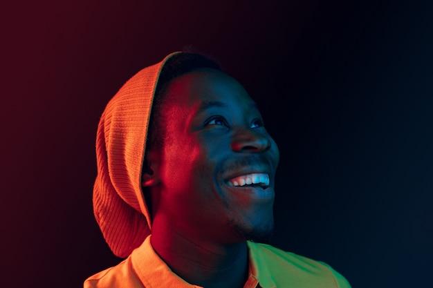 Chiuda sul ritratto di un giovane afroamericano felice che sorride contro il fondo nero dello studio del neon