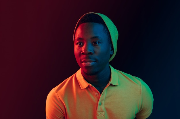 Chiuda sul ritratto di un giovane americano felice che sorride contro il muro di studio al neon nero