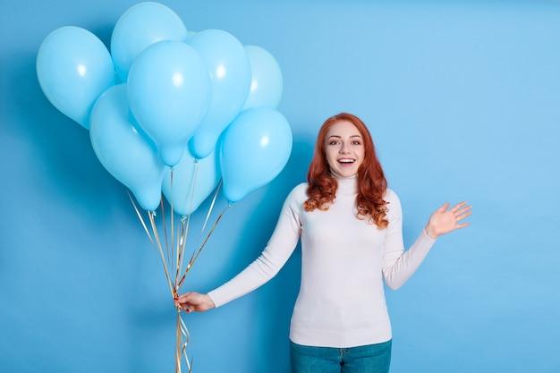Крупным планом портрет счастливой молодой красивой женщины в белой рубашке и джинсах