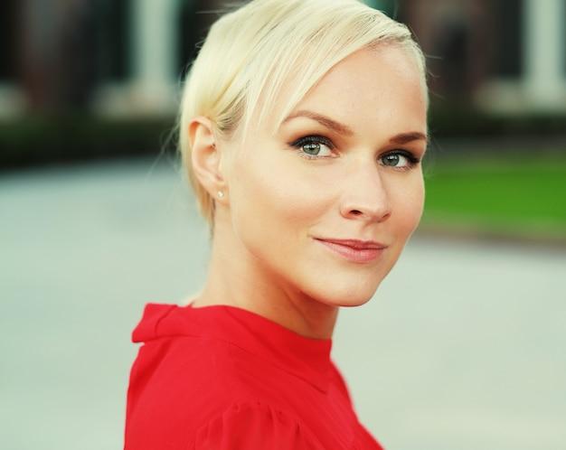 Крупным планом портрет счастливой молодой белокурой женщины, в красном платье, с веселой улыбкой.