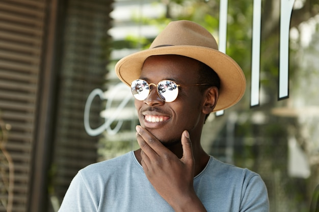 Close up portrait of happy young dark-skinned male tourist sitting at sidewalk cafe, touching his chin and smiling broadly, watching street performance, spending summer holidays in foreign cuntry