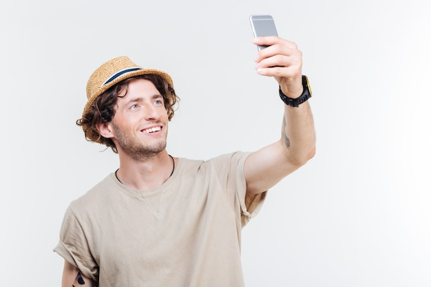 Close-up portrait of a happy young man making selfie photo on smartphone