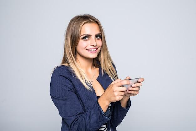 Chiuda sul ritratto di una giovane donna felice che gioca i giochi sul telefono cellulare isolato