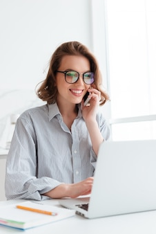 Close-up portrait of happy young woman in striped shirt talking on smartphone while using laptop computer at home