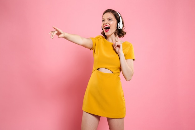 Close-up portrait of happy young woman in yellow dress and headphones pointing with finger, looking aside