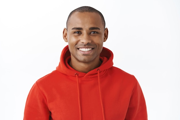 Close-up portrait of healthy good-looking african-american man in red hoodie, staying optimistic