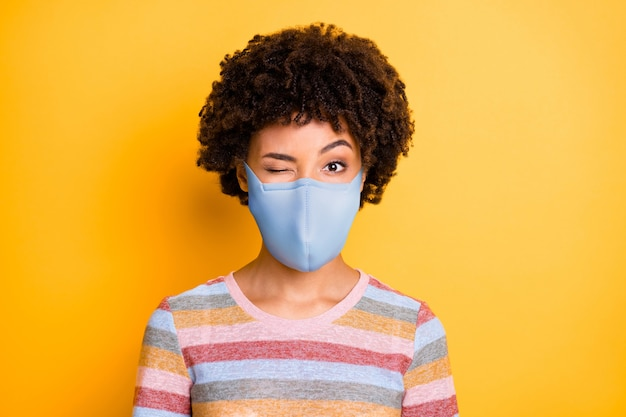 Close-up portrait of her she healthy attractive funky wavy-haired girl wearing safety reusable mask winking stop viral respiratory disease isolated bright vivid shine vibrant yellow color background