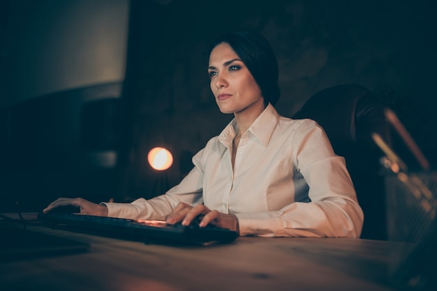 Close-up portrait of her she nice attractive busy lady top manager company owner typing creating financial presentation working on new it startup at night dark work place station indoors