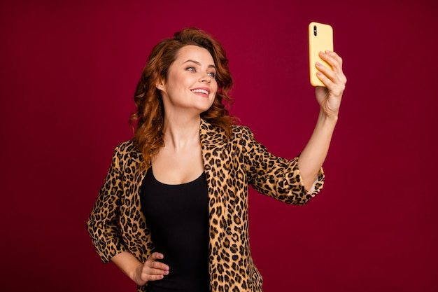 Close-up portrait of her she nice attractive charming lovely cheerful cheery wavy-haired girl taking making selfie posing having fun isolated on red maroon burgundy marsala color background