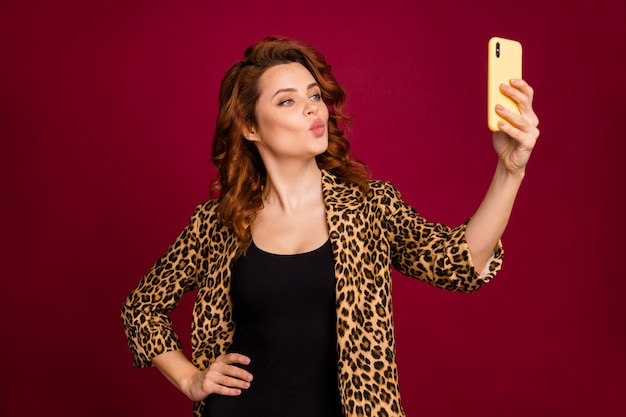 Close-up portrait of her she nice attractive charming pretty lovely lovable cheerful wavy-haired girl taking making selfie sending kiss isolated on red maroon burgundy marsala color background