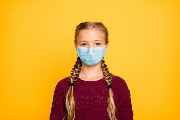Close-up portrait of her she nice attractive healthy pre-teen girl wearing safety gauze mask mers cov season influenza prevention isolated bright vivid shine vibrant yellow color background