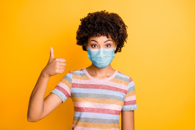 Close-up portrait of her she nice attractive healthy wavy-haired girl wearing safety gauze mask showing thumbup mers cov prevention isolated bright vivid shine vibrant yellow color background