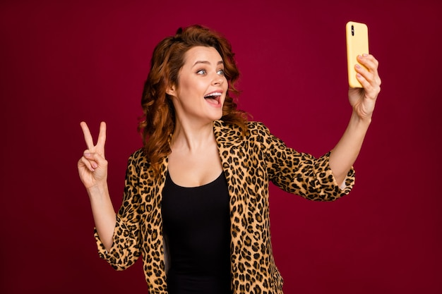 Close-up portrait of her she nice attractive lovely cheerful cheery glad wavy-haired girl taking making selfie showing v-sign isolated on red maroon burgundy marsala color background