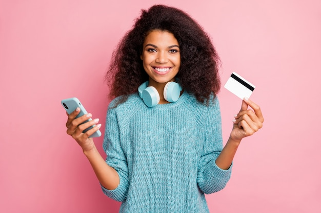 Close-up portrait of her she nice attractive lovely cheerful cheery wavy-haired girl holding in hands cell bank card wireless purchase buying shopping online isolated over pink pastel color wall