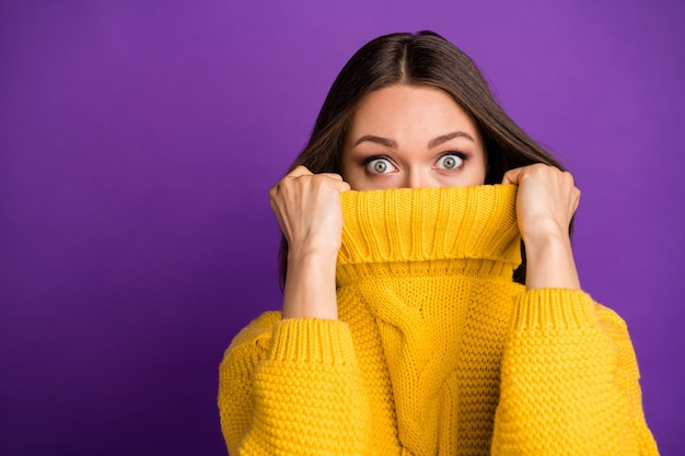 Close-up portrait of her she nice attractive lovely funny scared straight-haired girl hiding face in warm sweater .