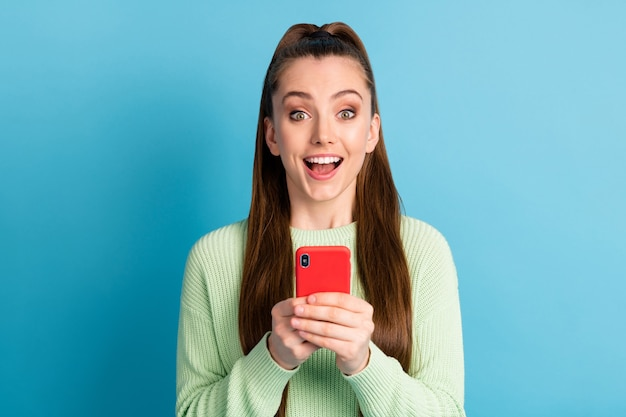Close-up portrait of her she nice attractive lovely pretty cheerful cheery amazed brown-haired girl using device fast speed 5g app isolated bright vivid shine vibrant blue color background