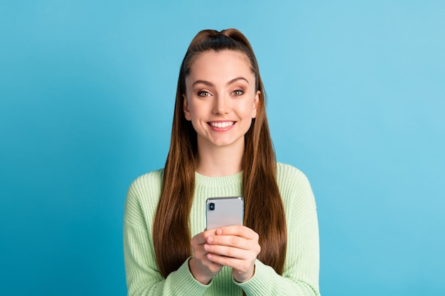 Close-up portrait of her she nice attractive lovely pretty cheerful cheery brown-haired girl using device browsing news smm comment isolated bright vivid shine vibrant blue color background