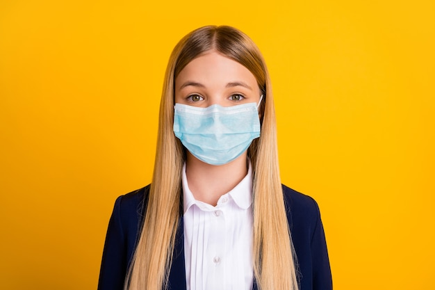 Close-up portrait of her she nice attractive pretty long-haired healthy schoolchild learner wearing safety gauze mask stop viral pneumonia isolated bright vivid shine vibrant yellow color background
