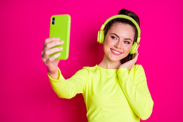 Close-up portrait of her she nice attractive pretty lovely cheerful glad girl listening music melody taking making selfie enjoying isolated bright vivid shine vibrant pink fuchsia color background