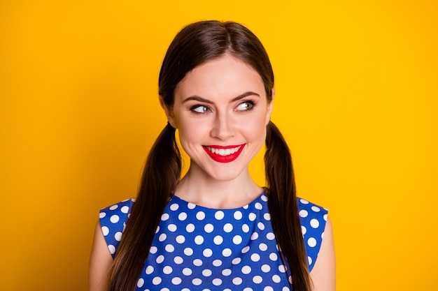 Close-up portrait of her she nice attractive pretty lovely glamorous cheerful girl wearing blue dotted blouse looking aside idea clue isolated over bright vivid shine vibrant yellow color background