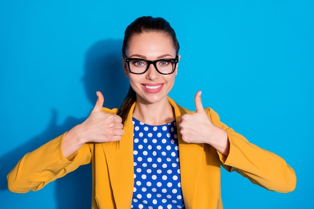 Close-up portrait of her she nice-looking attractive charming content cheerful cheery lady leader expert showing double thumbup advert isolated bright vivid shine vibrant blue color background