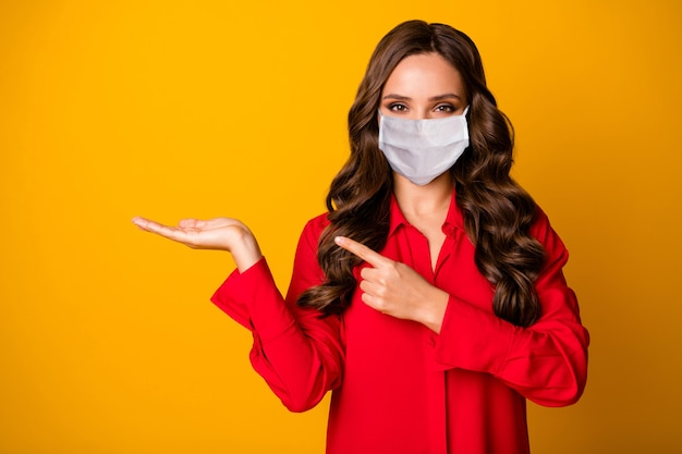 Close-up portrait of her she nice-looking attractive gorgeous wavy-haired girl wearing safety mask holding on palm showing copy space advert isolated bright vivid shine vibrant yellow color background