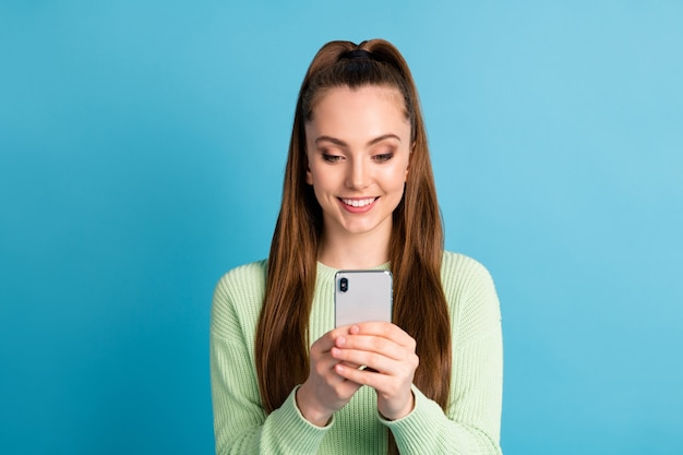 Close-up portrait of her she nice-looking attractive pretty lovely focused cheerful cheery brown-haired girl using device chatting isolated over bright vivid shine vibrant blue color background