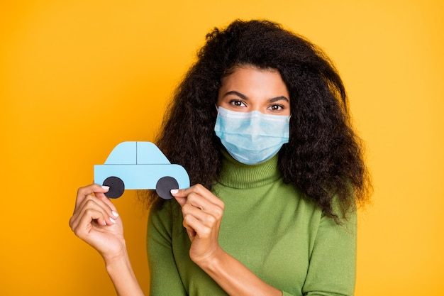 Close-up portrait of her she nice pretty wavy-haired girl wearing safety gauze mask mers cov prevention holding in hand paper card taxi cab isolated vibrant yellow color background