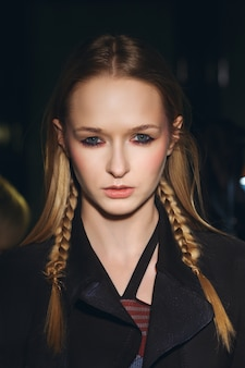 Close up portrait of hippie girl with pigtails in hair looking stern and wearing shabby coat
