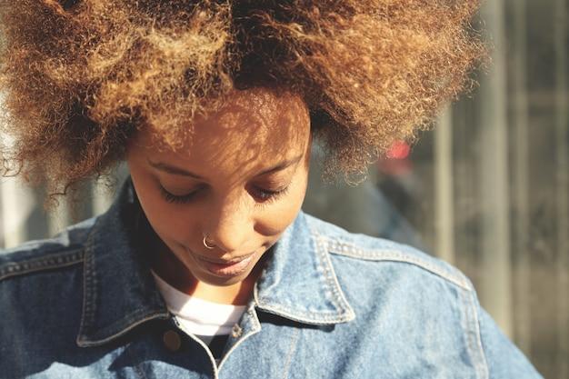 Close up ritratto di hipster ragazza dalla carnagione scura con taglio di capelli afro e anello al naso, vestita con una giacca di jeans alla moda, in posa all'aperto con gli occhi chiusi e un sorriso carino, godendo del bel tempo durante la passeggiata