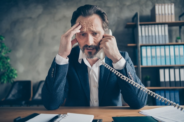Close-up portrait of his he depressed miserable jobless middle-aged guy employee talking on phone failure crisis staff reduction at modern loft industrial style interior workplace workstation