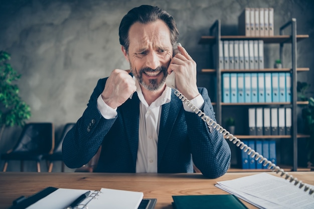 Close-up portrait of his he desperate depressed miserable fired jobless guy employee talking on phone fail failure anti crisis at modern loft industrial style interior workplace workstation