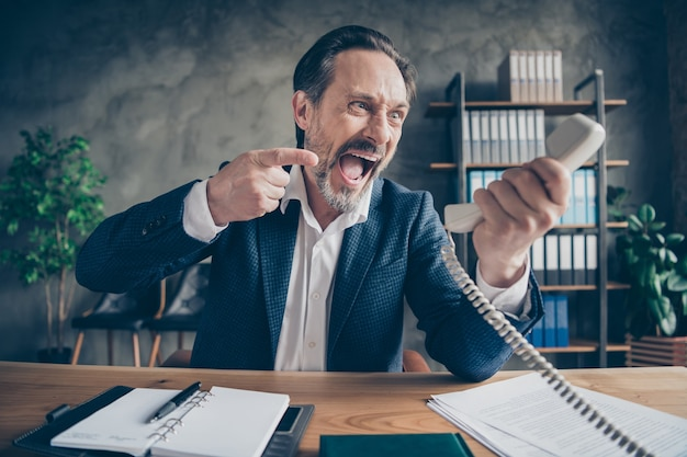 Close-up portrait of his he desperate furious fury evil jobless guy employer talking yelling on phone fight failure bad job at modern loft industrial style interior workplace workstation