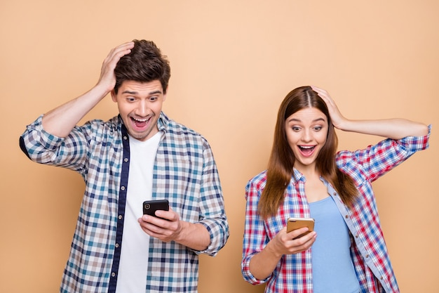 Close-up portrait of his he her she nice attractive charming amazed cheerful cheery glad couple wearing checked shirt using cell browsing fast speed 5g isolated over beige pastel color background