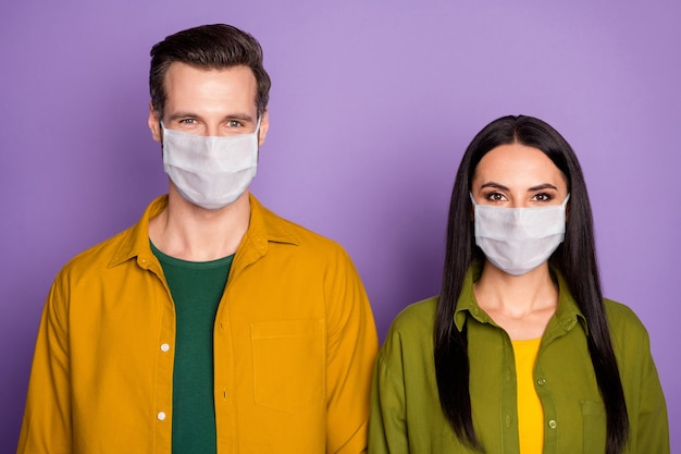 Close-up portrait of his he her she nice attractive couple wearing safety mask health care assistance insurance stop respiratory disease flu flue grippe isolated violet purple color background