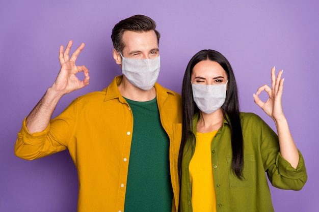 Close-up portrait of his he her she nice attractive healthy couple wearing safety mask health care insurance embracing showing ok-sign winking isolated violet purple color background
