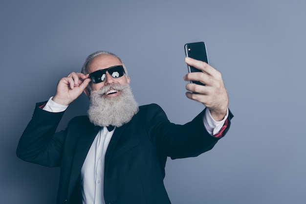 Close-up portrait of his he nice attractive chic classy cool trendy cheerful cheery gray-haired man touching specs taking making selfie influencer isolated over dark grey pastel color background