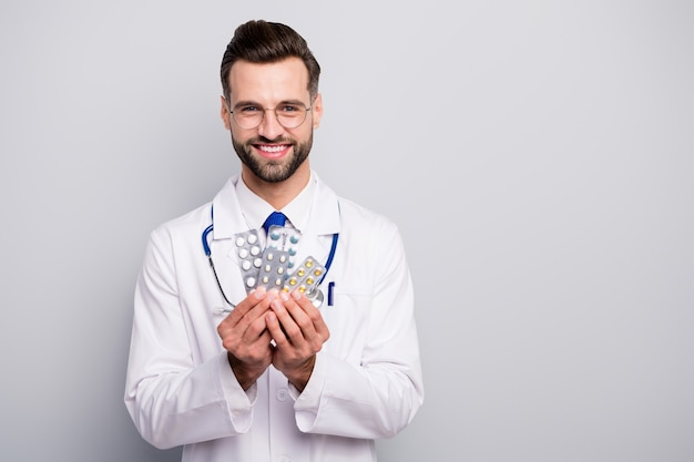 Close-up portrait of his he nice attractive glad cheerful cheery skilled professional doc holding in hands plates of tablets therapy solution isolated on light white gray pastel color