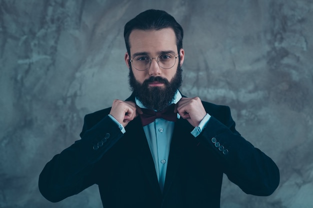 Close-up portrait of his he nice attractive imposing representative serious bearded guy wearing velvet tux fixing bow isolated over gray concrete industrial wall