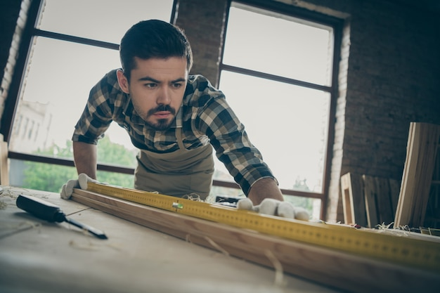 Close-up portrait of his he nice attractive serious concentrated focused skilled hardworking guy checking smoothness plank creating design project at modern industrial loft style interior studio