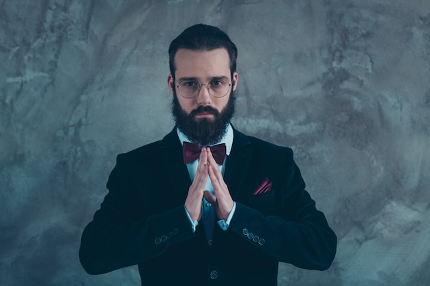 Close-up portrait of his he nice attractive well-dressed groomed serious bearded guy wearing velvet tux praying folded hands isolated over gray concrete industrial wall
