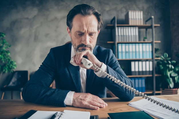 Close-up portrait of his he sullen depressed jobless guy finance director employee talking on phone cost reduction solution at modern loft industrial style interior workplace workstation