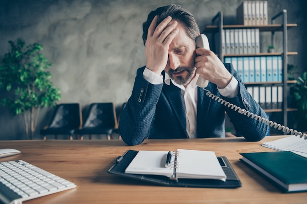Close-up portrait of his he sullen depressed miserable jobless middle-aged guy employee talking on phone crisis staff reduction at modern loft industrial style interior workplace workstation