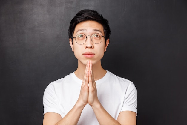 Close-up portrait of hopeful dreamy young asian guy in glasses and white t-shirt, hold hands together in pray, looking up pleading, anticipating miracle, awaiting results with hope