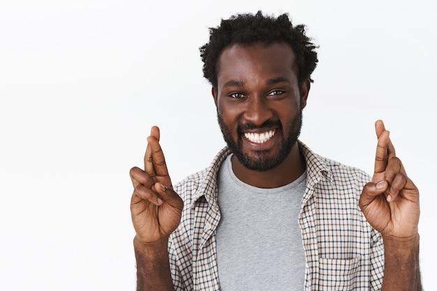 夢を信じる希望に満ちた、楽観的で陽気なアフリカ系アメリカ人のひげを生やした男性のクローズアップの肖像画が実現します