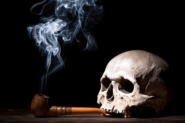 Close up portrait of human skull with smoking pipe and smoke on black background