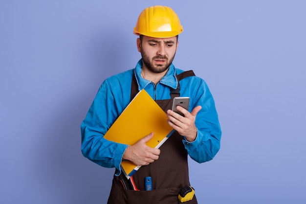 Close up portrait of indignated confused young engineer holding smartphone and papercase, having shocked facial expression, getting message with bad news. job losses during quaratine. crisis concept.