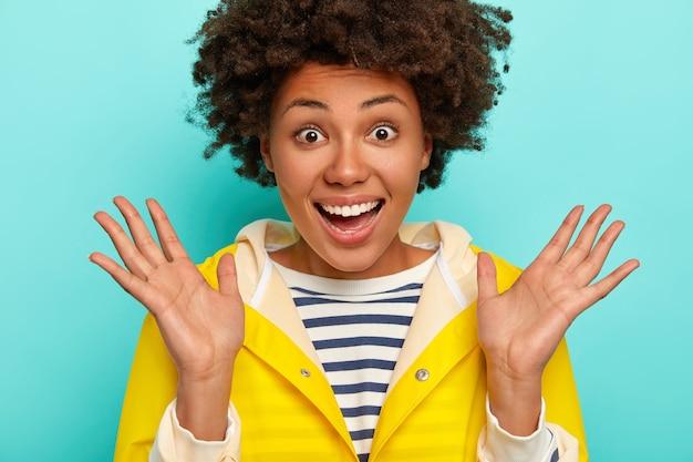 Close up ritratto di gioiosa femmina dalla pelle scura alza i palmi, si sente felicissima, reagisce alla sorpresa, sorride ampiamente, mostra i denti bianchi, indossa un impermeabile giallo ha camminato durante il periodo autunnale isolato sul blu