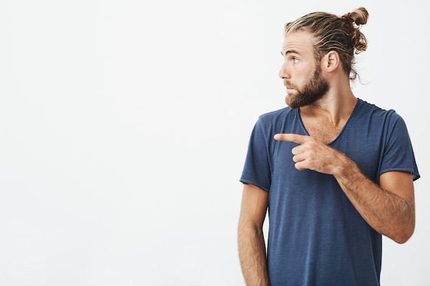 Close up portrait of joyful handsome guy with trendy haircut and beard in profile pointing his finger at white copyspace