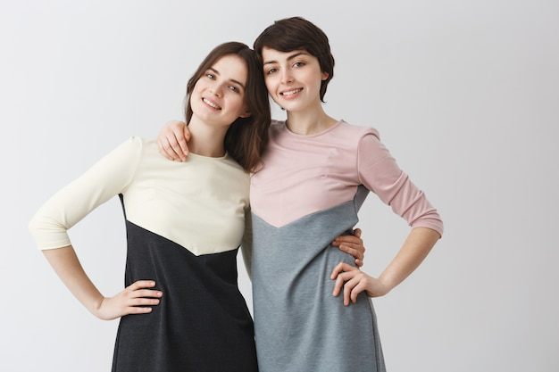 Close up portrait of joyful lesbian couple hugging each other, holding hand on waist, posing for photo in matching outfits.